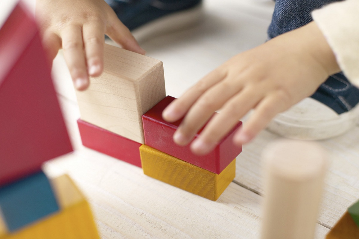 Girl Playing With Building Blocks --- Image by © Royalty-Free/Corbis